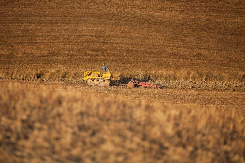 犁麦子亩茬地的农夫拖拉机和 耕种,农业 免版税库存照片