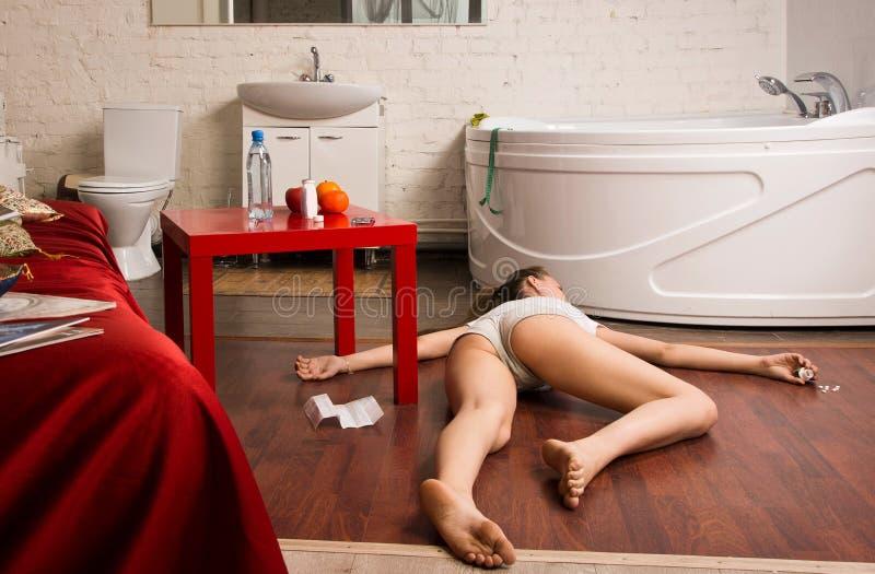 犯罪现场模仿。说谎在地板上的被超剂量的女孩 库存照片
