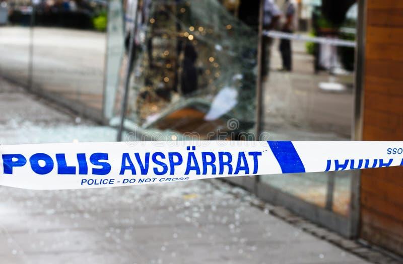 犯罪现场调查警察不横渡界限磁带调查的警察队,商店是抢劫 免版税库存图片