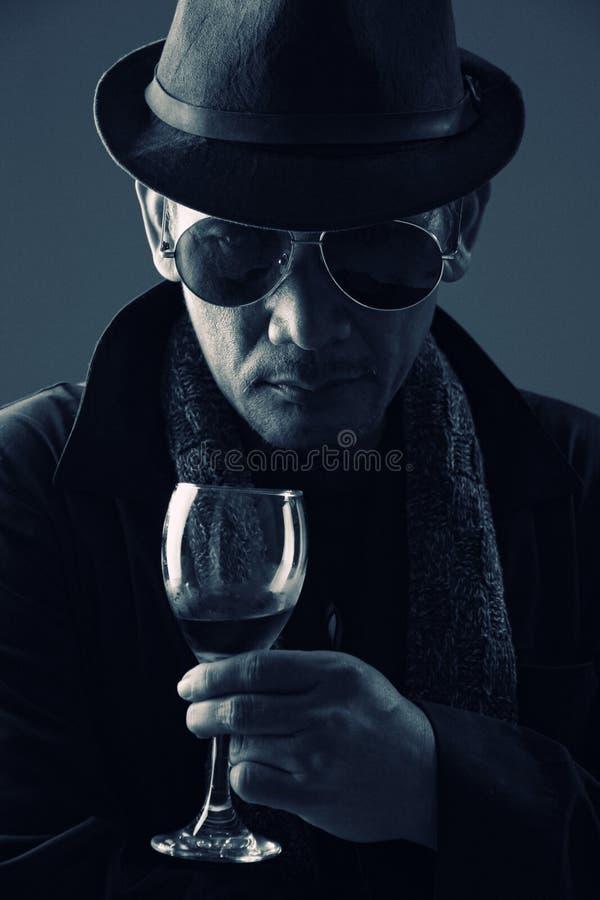 犯罪策划者和一杯酒 免版税图库摄影