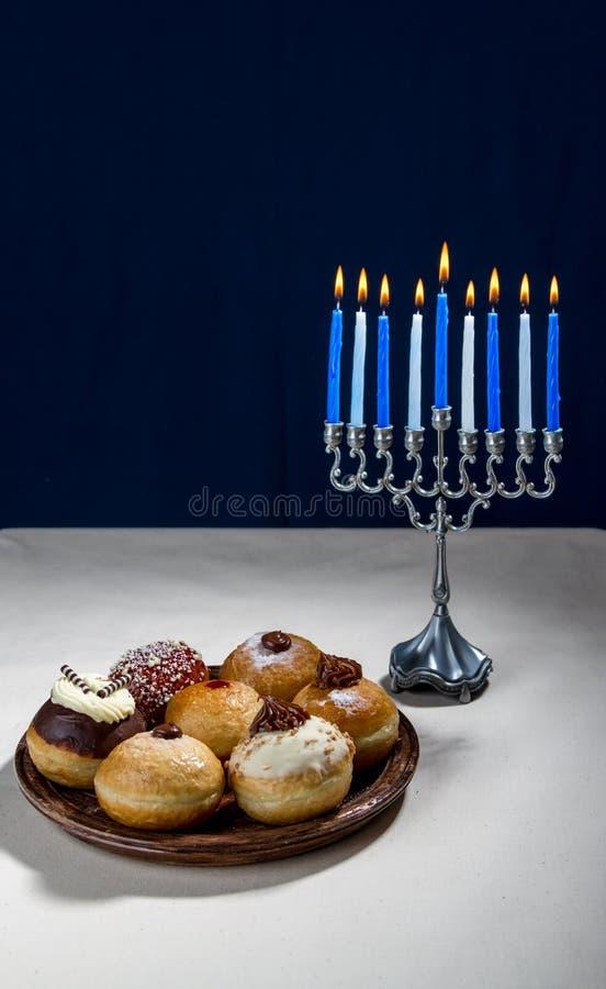 犹太假日光明节、光明节menorah和sufganiyot 免版税库存照片