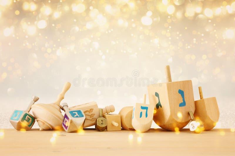 犹太假日光明节横幅与木dreidels & x28的; 转动的top& x29;在闪烁发光的背景 免版税库存图片