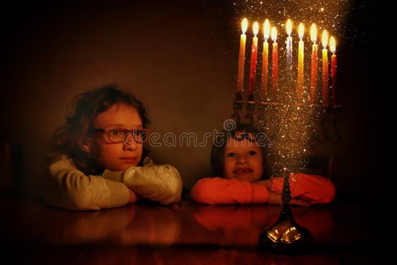 犹太假日光明节背景的低调图象与看menorah传统大烛台的两个逗人喜爱的孩子的 免版税图库摄影