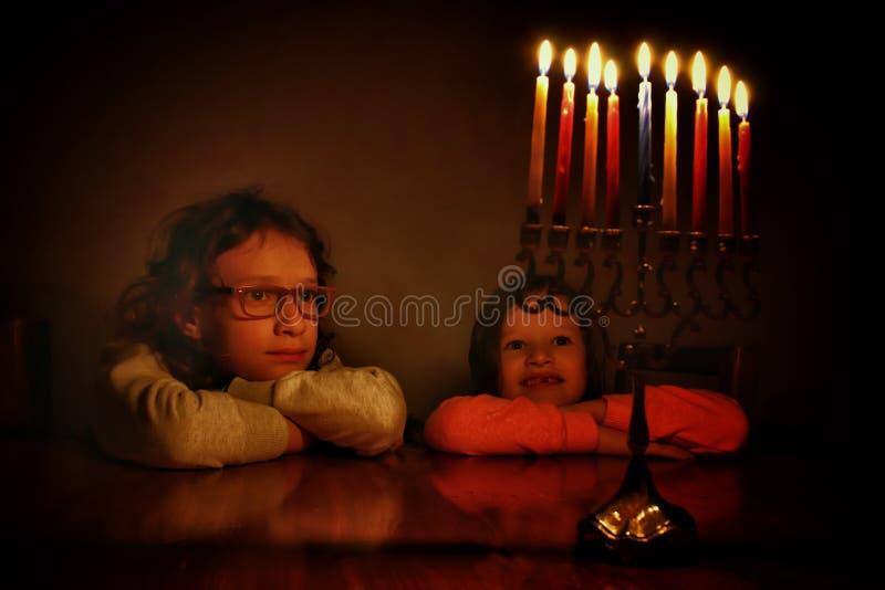犹太假日光明节背景的低调图象与看menorah & x28的两个逗人喜爱的孩子的; 传统candelabra& x29; 图库摄影