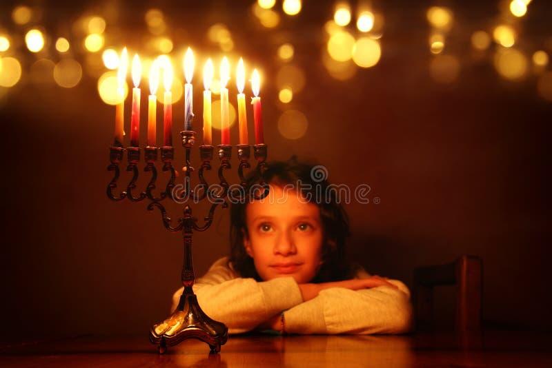 犹太假日光明节背景的低调图象与看menorah & x28的逗人喜爱的女孩的; 传统candelabra& x29; 免版税库存照片
