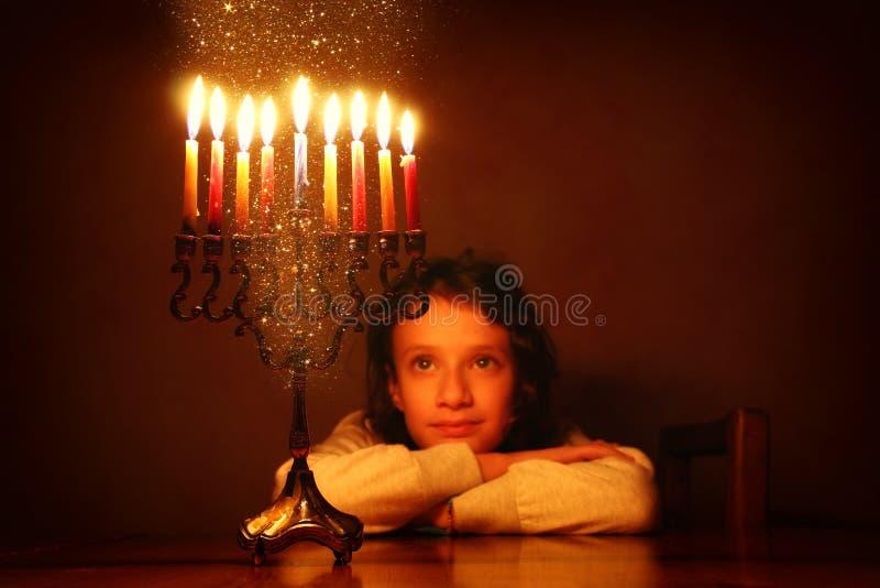 犹太假日光明节背景的低调图象与看menorah & x28的逗人喜爱的女孩的; 传统candelabra& x29; 免版税库存图片
