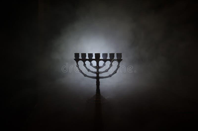 犹太假日光明节背景的低调图象与menorah的在黑暗的被定调子的有雾的背景 库存照片