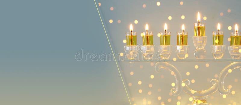 犹太假日光明节背景的图象与水晶menorah & x28的; 传统candelabra& x29;并且蜡烛 免版税库存图片