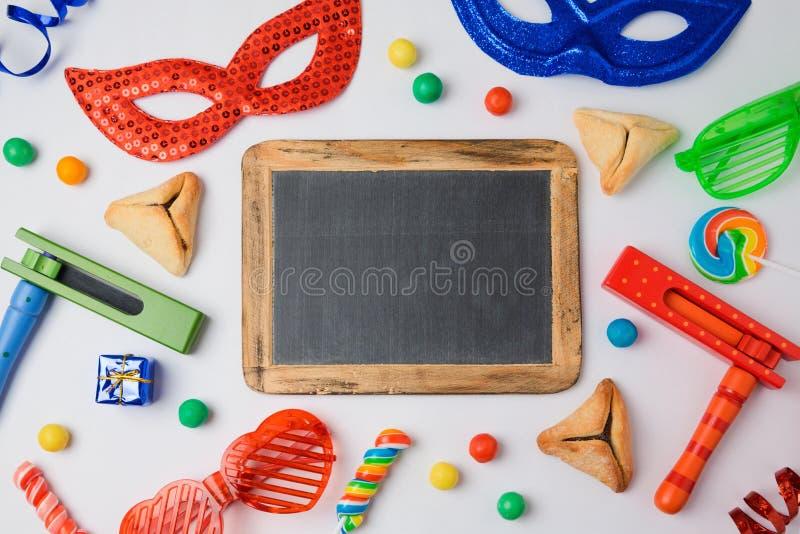 犹太假日普珥节概念与hamantaschen曲奇饼、狂欢节面具和黑板在白色背景 免版税库存图片