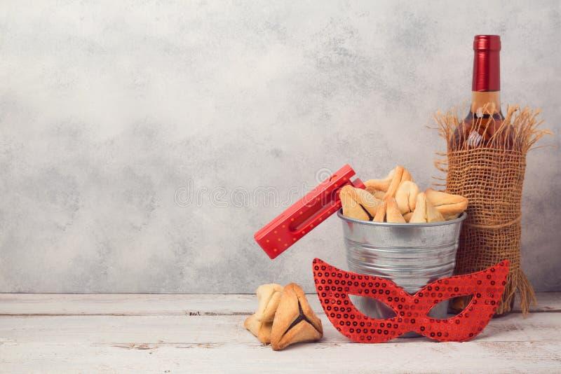 犹太假日普珥节概念与hamantaschen曲奇饼或hamans耳朵、狂欢节面具和酒瓶 库存图片