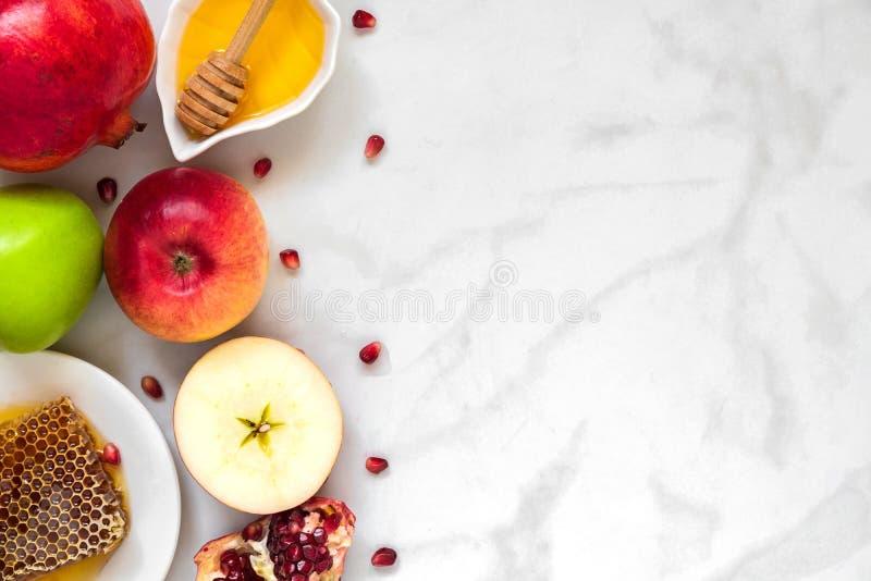犹太假日Rosh Hashana背景用蜂蜜、石榴和苹果 平的位置 顶视图 免版税库存图片