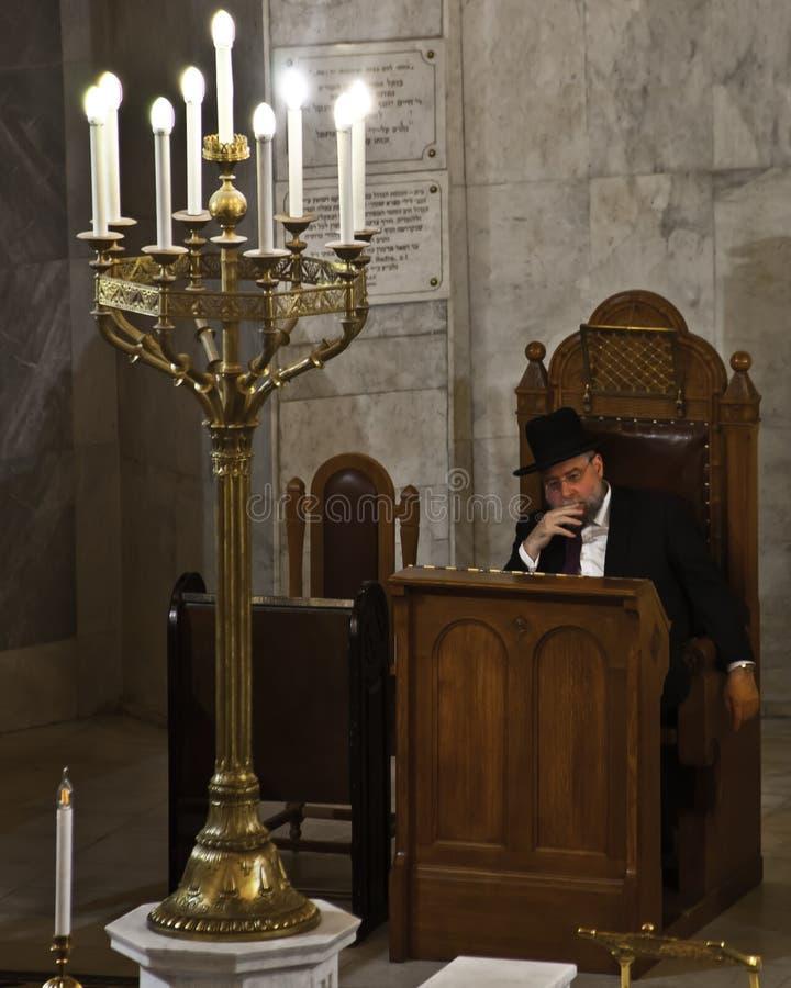 犹太教教士在一张高脚椅子坐并且考虑某事在 库存照片