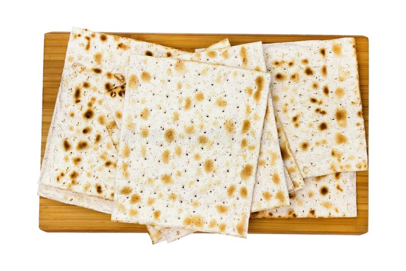犹太matza,在白色背景隔绝的被发酵的面包一张顶上的照片在木砧板的 照片从上面 免版税库存照片