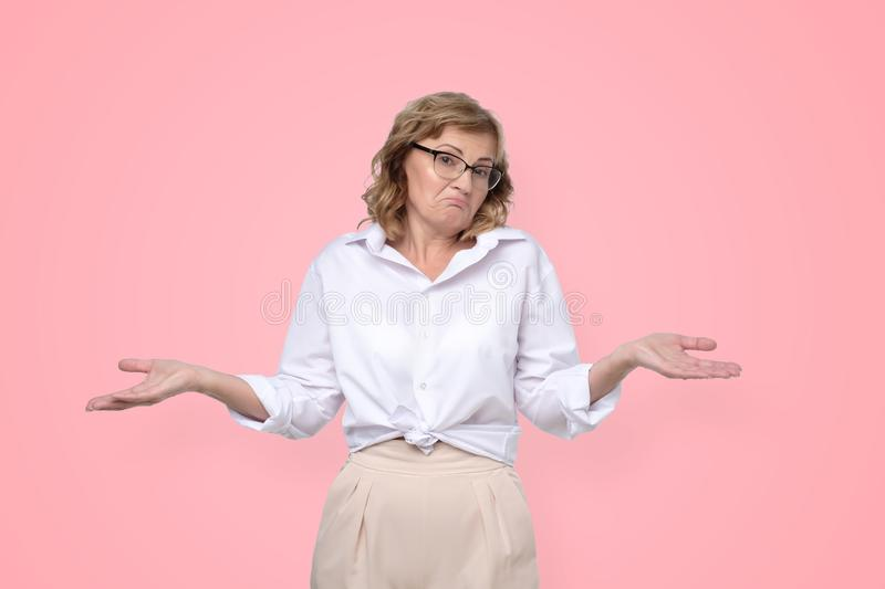 犹豫的成熟白种人独裁的妇女耸肩肩膀,看起来不定和迷茫 免版税库存图片