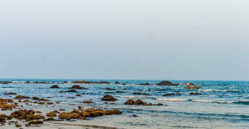 狂放的空的热带海滩,蓝天,在岸的阳光reflextions在日落时间在一个晴天当风景样式 免版税库存图片