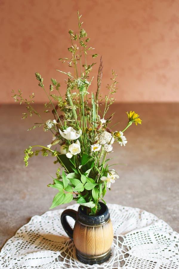 狂放的草甸花束在陶瓷花瓶开花 库存照片