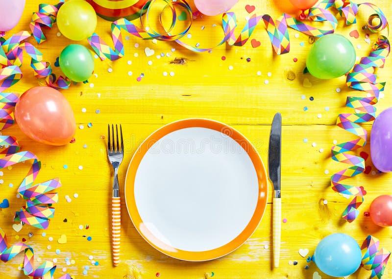 狂欢节季节的明亮的黄色餐位餐具 免版税库存照片