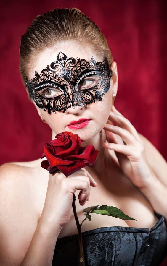 狂欢节屏蔽的美丽的妇女与红色起来了 免版税库存照片