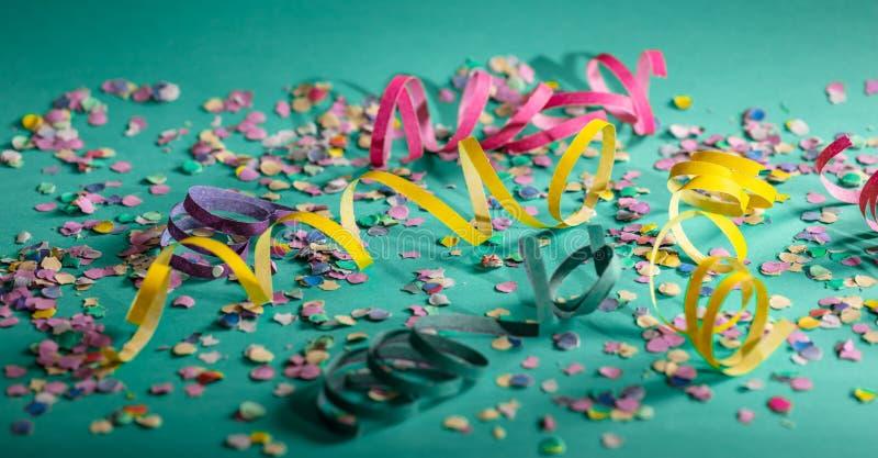 狂欢节或生日宴会、五彩纸屑和蛇纹石在鲜绿色的背景 免版税库存图片