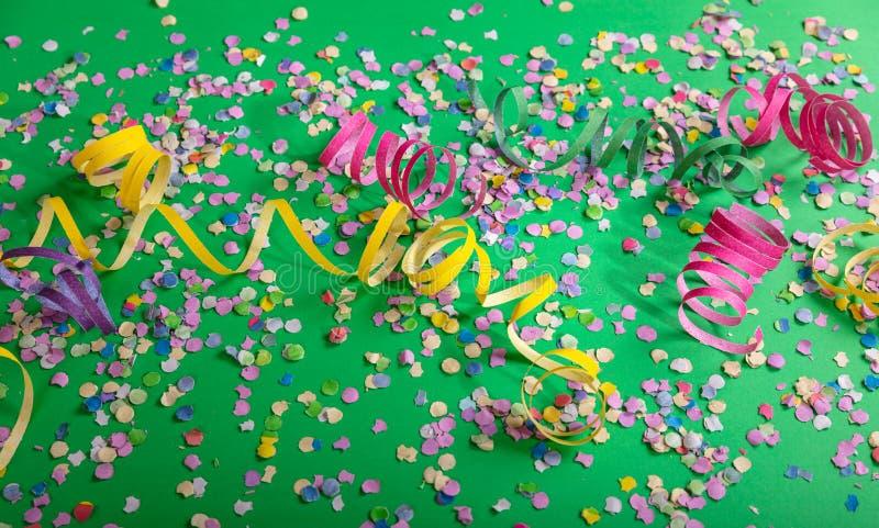 狂欢节或生日宴会、五彩纸屑和蛇纹石在鲜绿色的背景 图库摄影