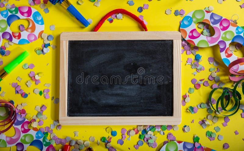 狂欢节或生日聚会 空白的黑板、五彩纸屑和蛇纹石在明亮的黄色背景 免版税库存图片