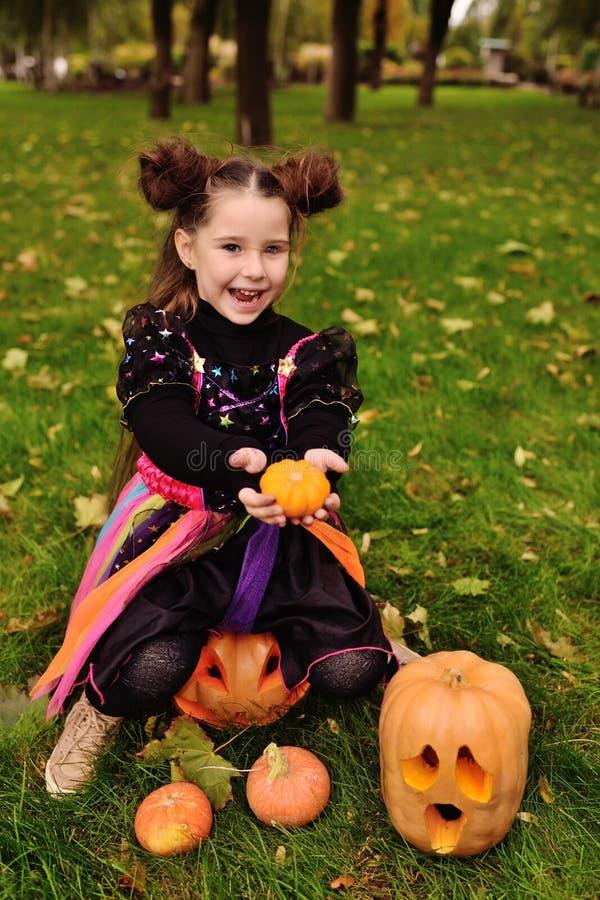 狂欢节服装的小女孩用南瓜庆祝万圣夜的 库存图片