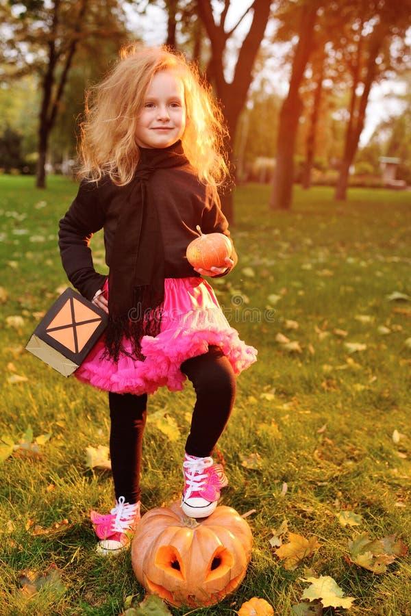狂欢节服装的小女孩用南瓜庆祝万圣夜的 免版税库存图片