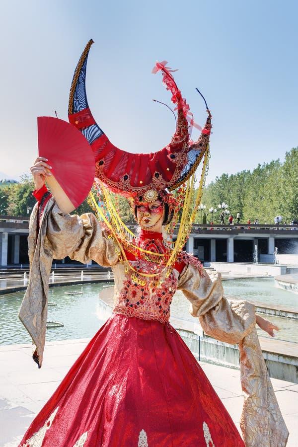 狂欢节服装的美丽的女孩和反对蓝天的一个威尼斯式面具在一个晴天 免版税库存图片