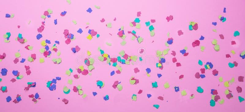 狂欢节,生日宴会 在桃红色背景的五颜六色的五彩纸屑 免版税库存照片