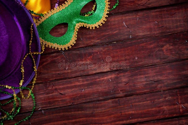 狂欢节:面具和紫色帽子有木背景 库存图片