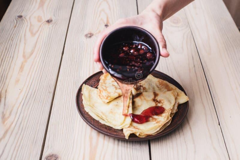 狂欢节 俄国薄煎饼倾吐山莓果酱 木的表 图库摄影
