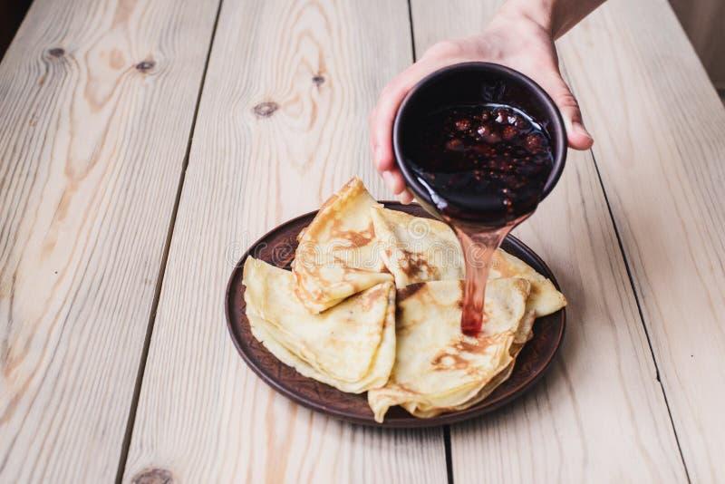 狂欢节 俄国薄煎饼倾吐山莓果酱 木的表 库存图片