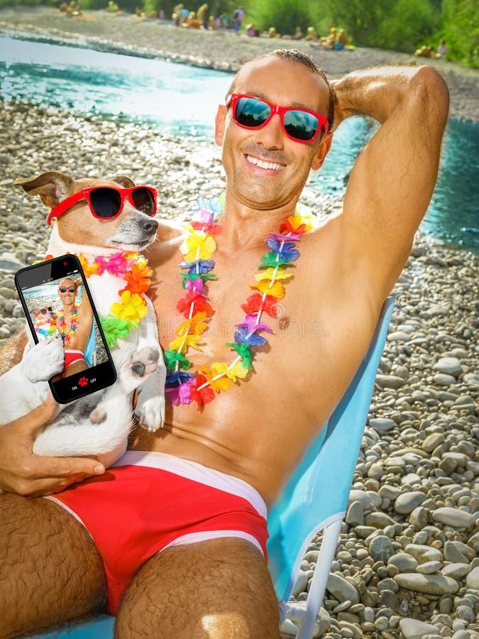 狗和所有者在海滩selfie 免版税图库摄影