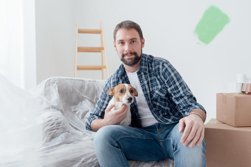 狗所有者在他的新房里 免版税库存照片