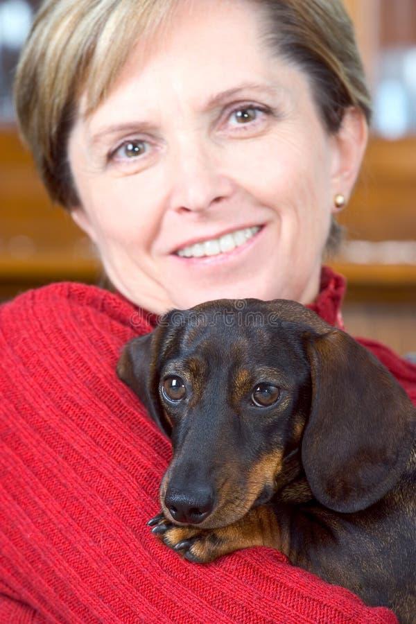 狗拿着成熟妇女 免版税图库摄影