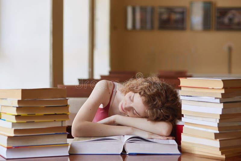 狡猾的头发的女生睡着,当找到的信息看书,为检查做准备,laing在桌上的妇女,时 库存图片