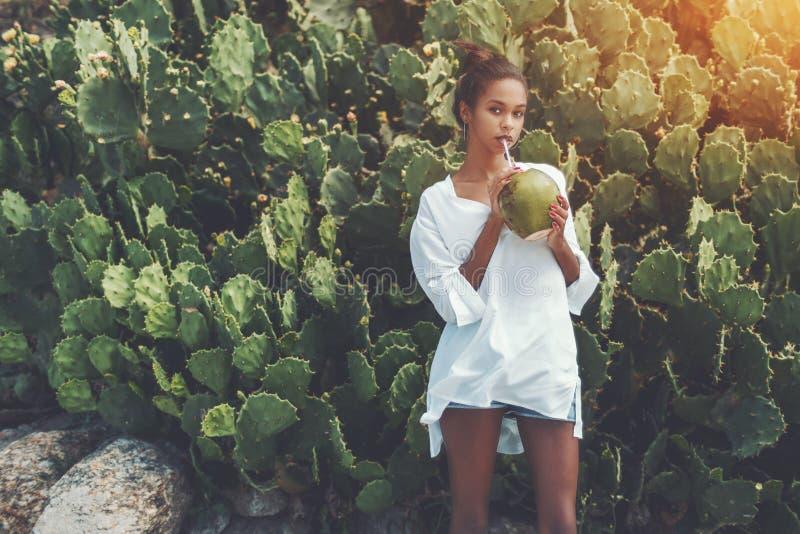 狡猾的黑人女孩用新鲜的椰子 库存图片
