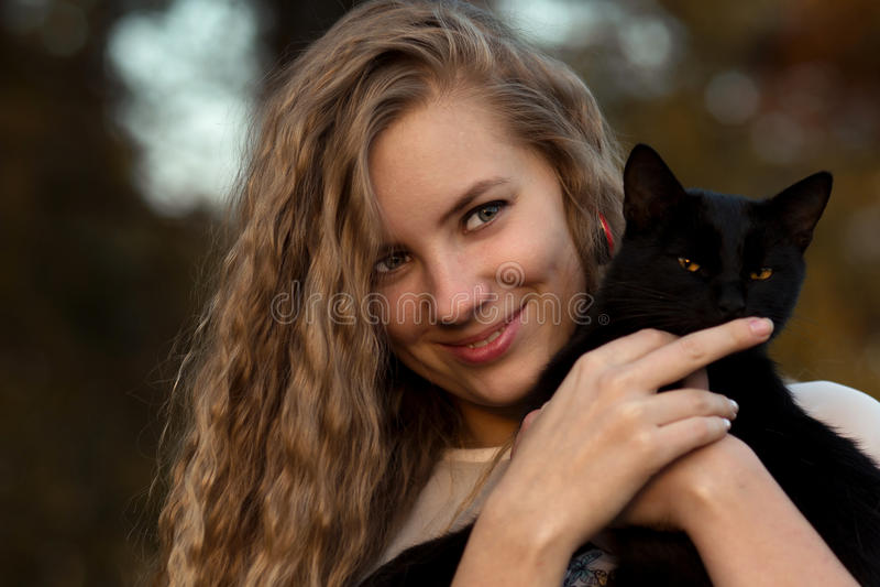 狡猾,美丽,嬉戏,棘手,狡猾,爱抚并且拿着恶意嘘声 女孩爱宠物 宠物是朋友 猫是朋友给人 免版税库存图片