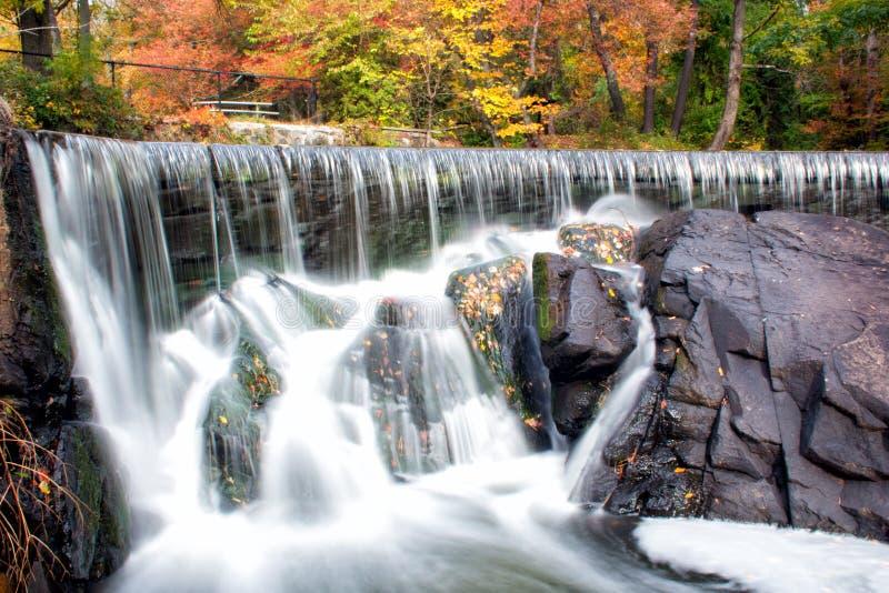 狩猎在秋叶季节期间的磨房瀑布 库存照片