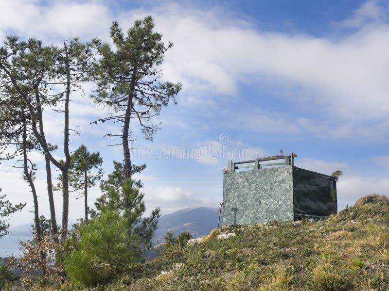 狩猎小屋被伪装在狂放的小山顶部 免版税库存照片