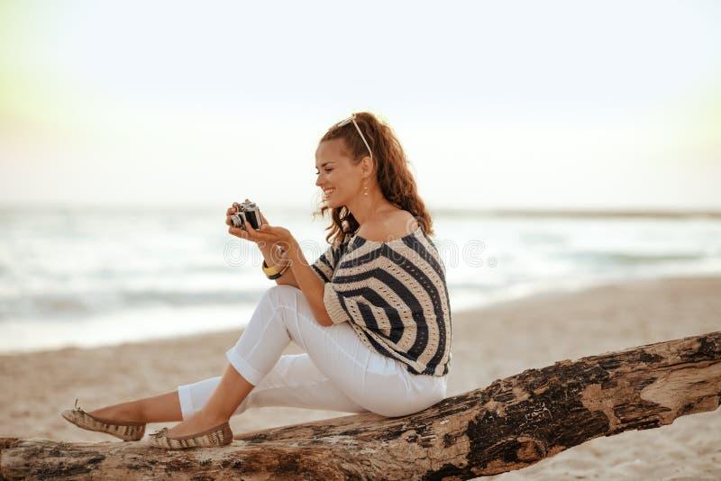 独奏在照相机的旅行家妇女观看的照片 免版税库存照片