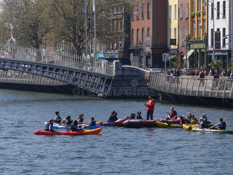 独木舟的人们由Ha `在利菲河的便士桥梁在都伯林市,爱尔兰 免版税库存图片
