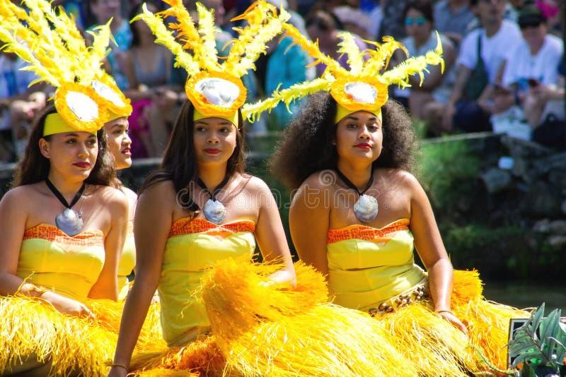 独木舟的Tahitian舞蹈家漂浮在玻利尼西亚文化中心 免版税库存照片