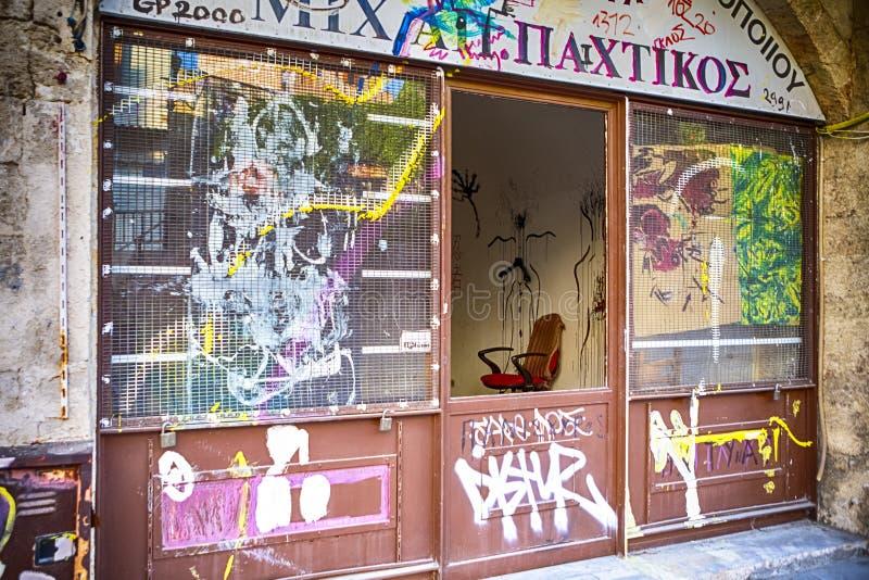独特的五颜六色的议院和克里特岛人Grafiti艺术在其中一家被放弃的商店中在干尼亚州 免版税库存图片