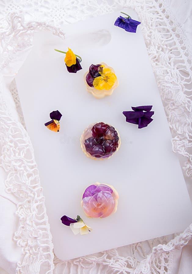 独特的日本点心果冻和巴伐利亚奶油Havaro与可食的紫罗兰色花 明胶健康吃点心 顶视图 库存照片