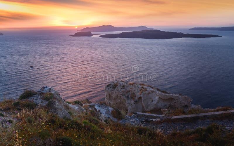 独特的海视图到日落的硫磺群岛卡美尼岛,圣托里尼,希腊 免版税图库摄影