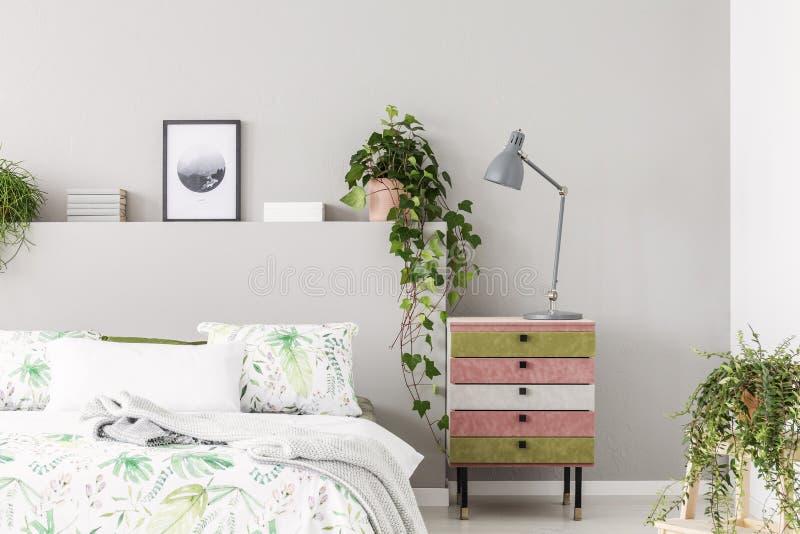独特的绒面革用灰色灯报道了nightstand在有都市密林的,在空的灰色墙壁上的拷贝空间明亮的斯堪的纳维亚卧室 库存照片