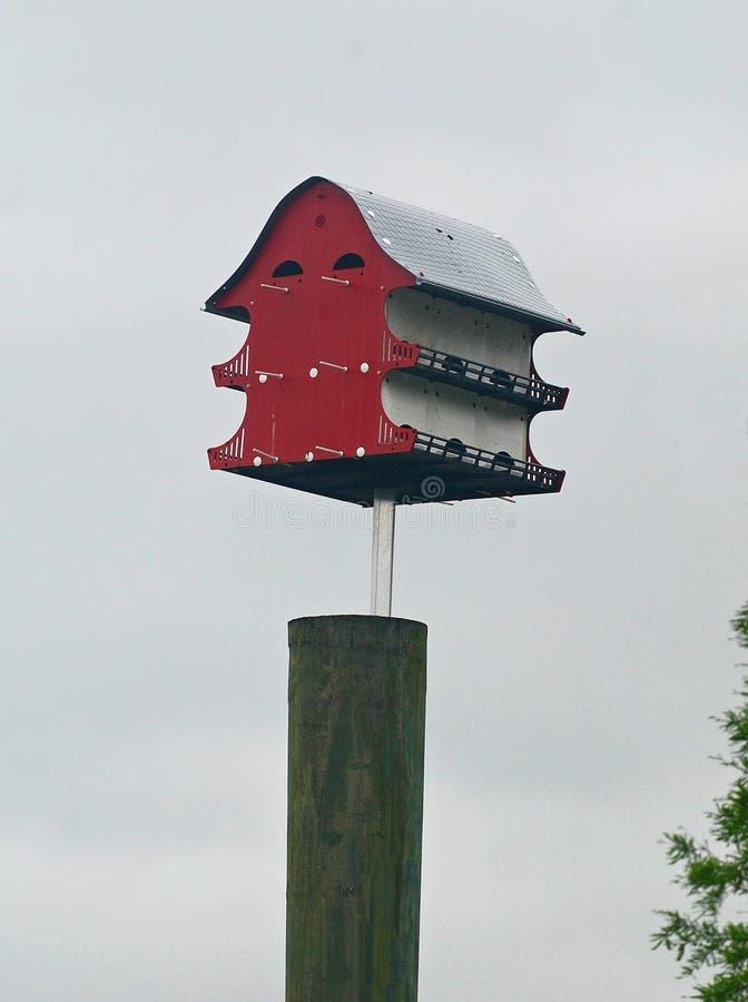 独特,红色,三层的公寓类型鸟房子 免版税库存图片