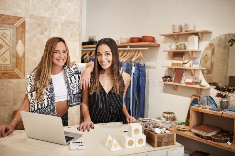 独立衣物和礼品店两位女性店主画象在销售书桌后的 库存图片