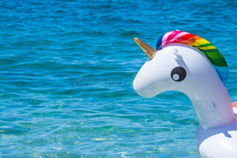 独角兽在水背景的游泳管 可膨胀的独角兽 幻想夏天水池或海的游泳圆环 活跃滑稽 库存照片